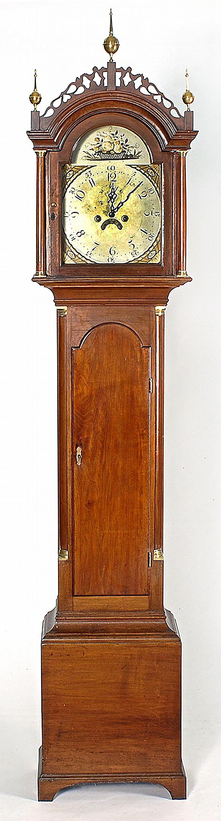 ANTIQUE AMERICAN TALL-CASE CLOCK In mahogany. Brass ball and spire finials above fenestrated fretwork. Bonnet supported by full untu...