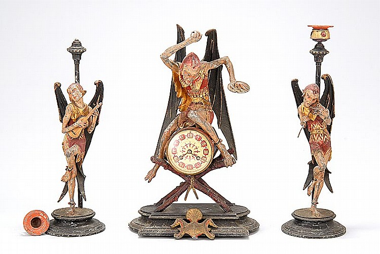 UNUSUAL THREE-PIERCE MANTEL GARNITURE SET Includes a clock and two candlesticks in mixed metals, each with a winged figure of Satan...