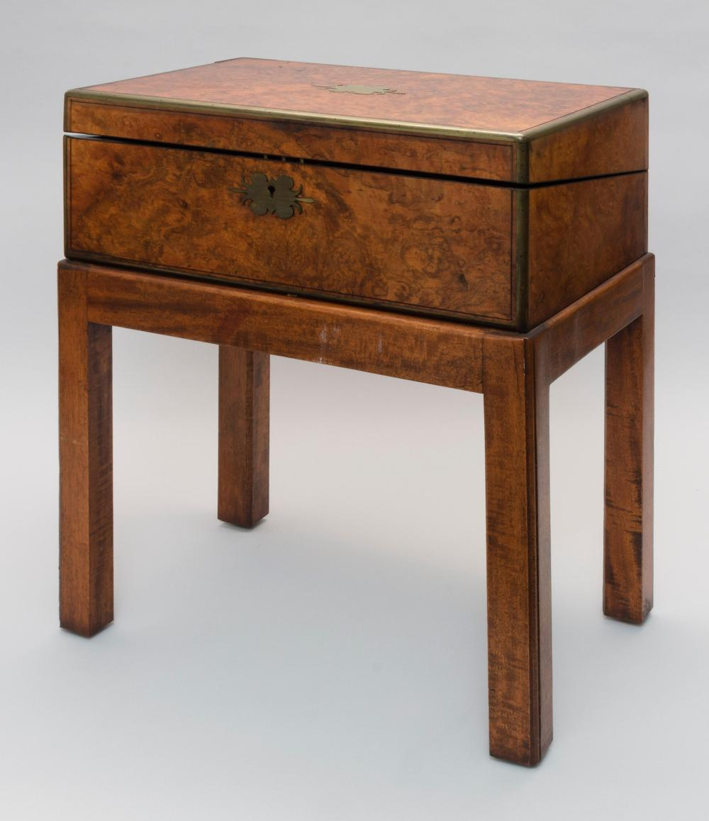"""BRASS-BOUND BURLWOOD LAP DESK ON STAND With fitted interior. 20th Century wooden stand. Height 20.5"""". Width 16"""". Depth 10.5""""."""