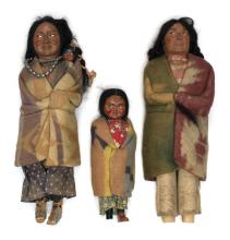 THREE SKOOKUM DOLLS In the form of American Natives in traditional dress. Lengths from 9.5