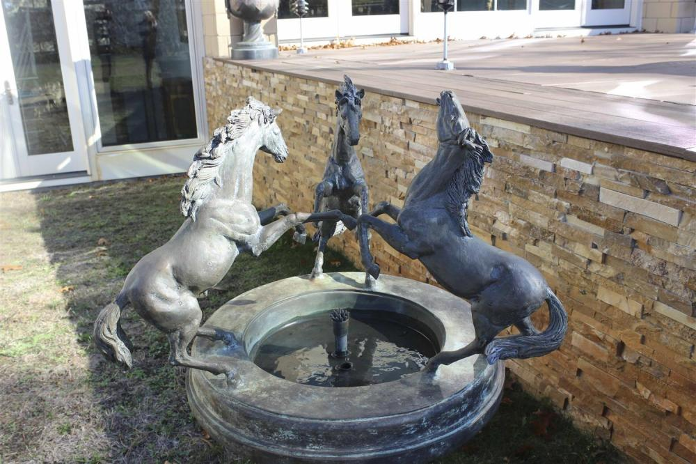 BRONZE GARDEN FOUNTAIN In the form of three bucking horses along the perimeter of a bird bath, with a reeded columnar pedestal and a...