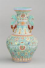 POLYCHROME PORCELAIN VASE In baluster form with dragon's-head and loose ring handles. Body decorated with flowers and vines on a tur...