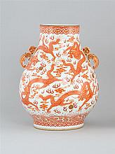 CORAL-RED DECORATED PORCELAIN VASE In pear shape with five-claw dragon design and stylized dragon handles. Six-character Qianlong ma...