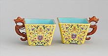 PAIR OF PORCELAIN CUPS In square form with dragon handles. Exterior decorated with passionflower and shou on a yellow ground. Interi...