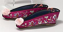 VIOLET-COLORED SILK MANCHU SLIPPERS With multicolored silk embroidered design of mandarin ducks and Symbol of Happiness. Pink cotton...