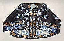 EMBROIDERED SILK JACKET In blue floral pattern on a dark blue ground. Gilt-bronze buttons.