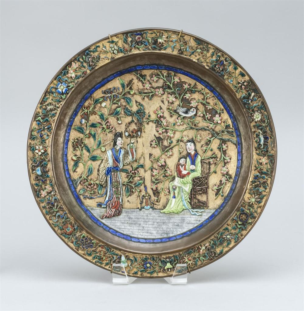 "CHINESE ENAMEL-ON-COPPER PLAQUE Floral border surrounds a scene of figures in a garden. Marked ""Made in China"" on base. Diameter 12""."