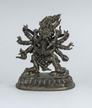Lot 921: CHINESE SILVERED BRONZE FIGURE OF MAHAKALA WITH HIS CONSORT Mahakala with eight arms and six legs dancing on four prostrate figures....