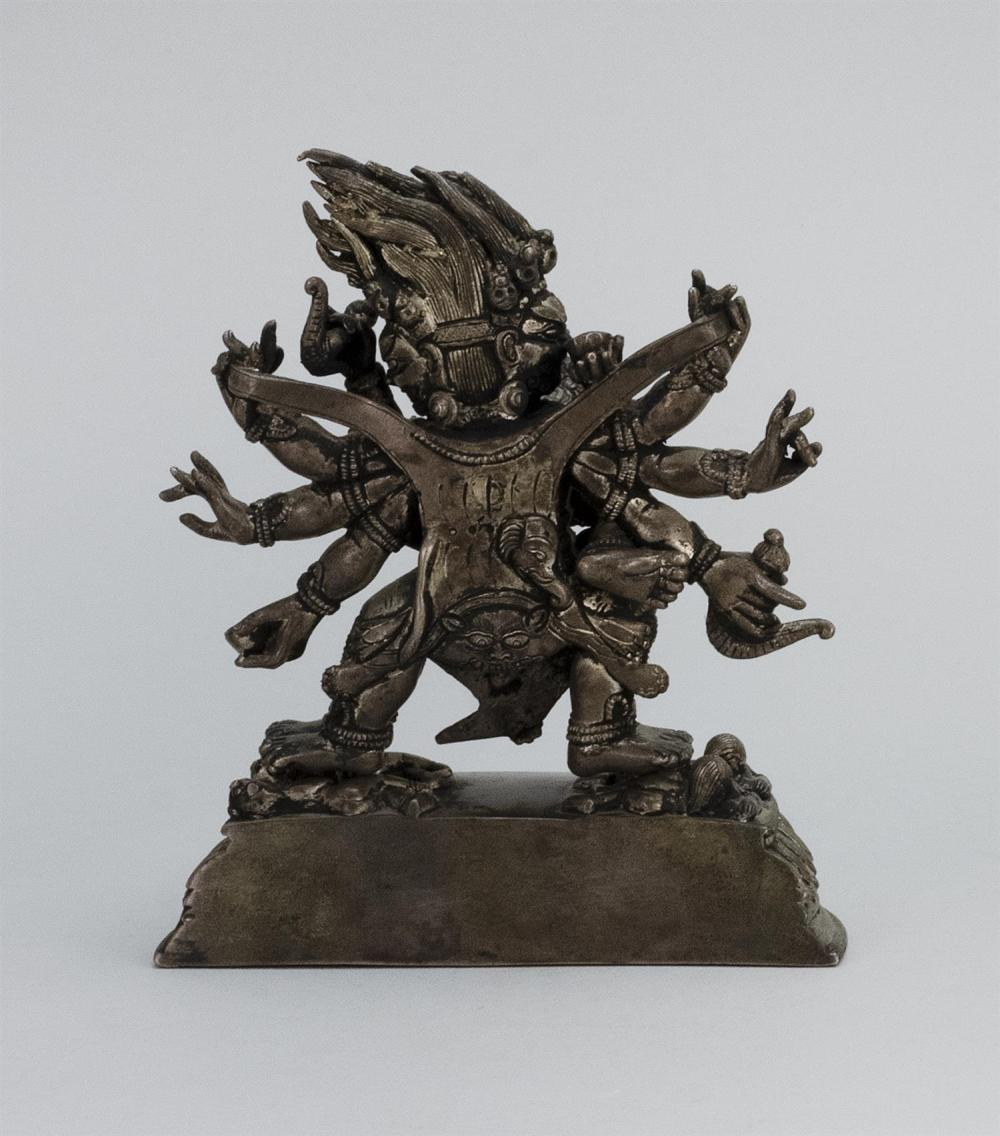 CHINESE SILVERED BRONZE FIGURE OF MAHAKALA WITH HIS CONSORT Mahakala with eight arms and six legs dancing on four prostrate figures....