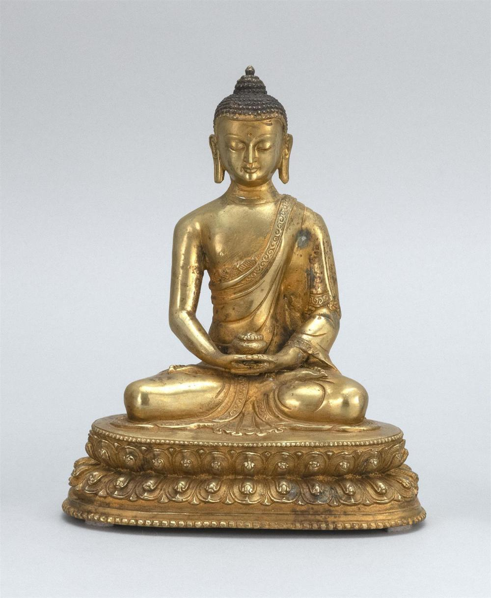 "SINO-TIBETAN GILT-BRONZE FIGURE OF BUDDHA Seated in lotus posture on a two-tier lotus base and holding a censer. Height 7.8""."