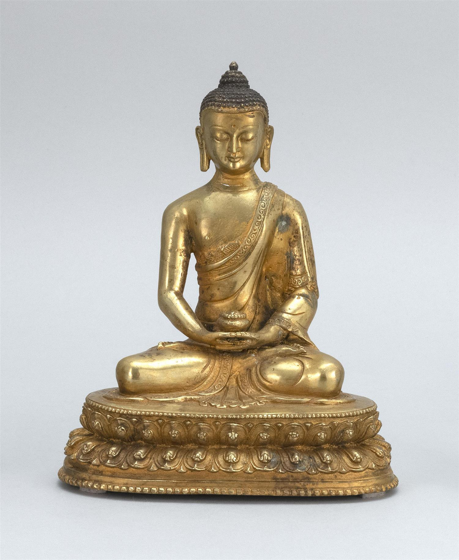 """SINO-TIBETAN GILT-BRONZE FIGURE OF BUDDHA Seated in lotus posture on a two-tier lotus base and holding a censer. Height 7.8""""."""