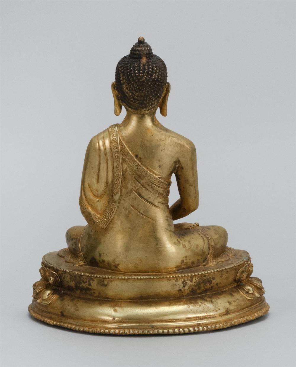 SINO-TIBETAN GILT-BRONZE FIGURE OF BUDDHA Seated in lotus posture on a two-tier lotus base and holding a censer. Height 7.8