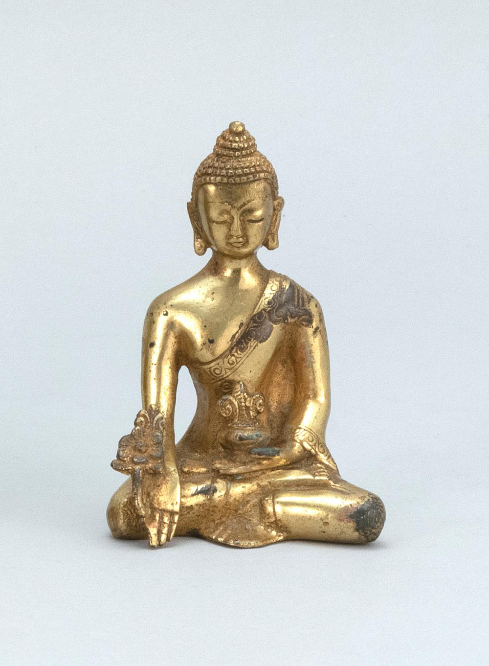 "CHINESE GILT-BRONZE FIGURE OF BUDDHA Seated in earth touching posture and holding a censer and a flower blossom. Height 4.2""."