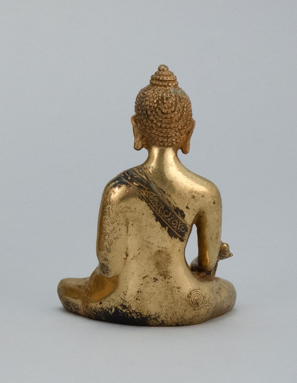 "Lot 923: CHINESE GILT-BRONZE FIGURE OF BUDDHA Seated in earth touching posture and holding a censer and a flower blossom. Height 4.2""."