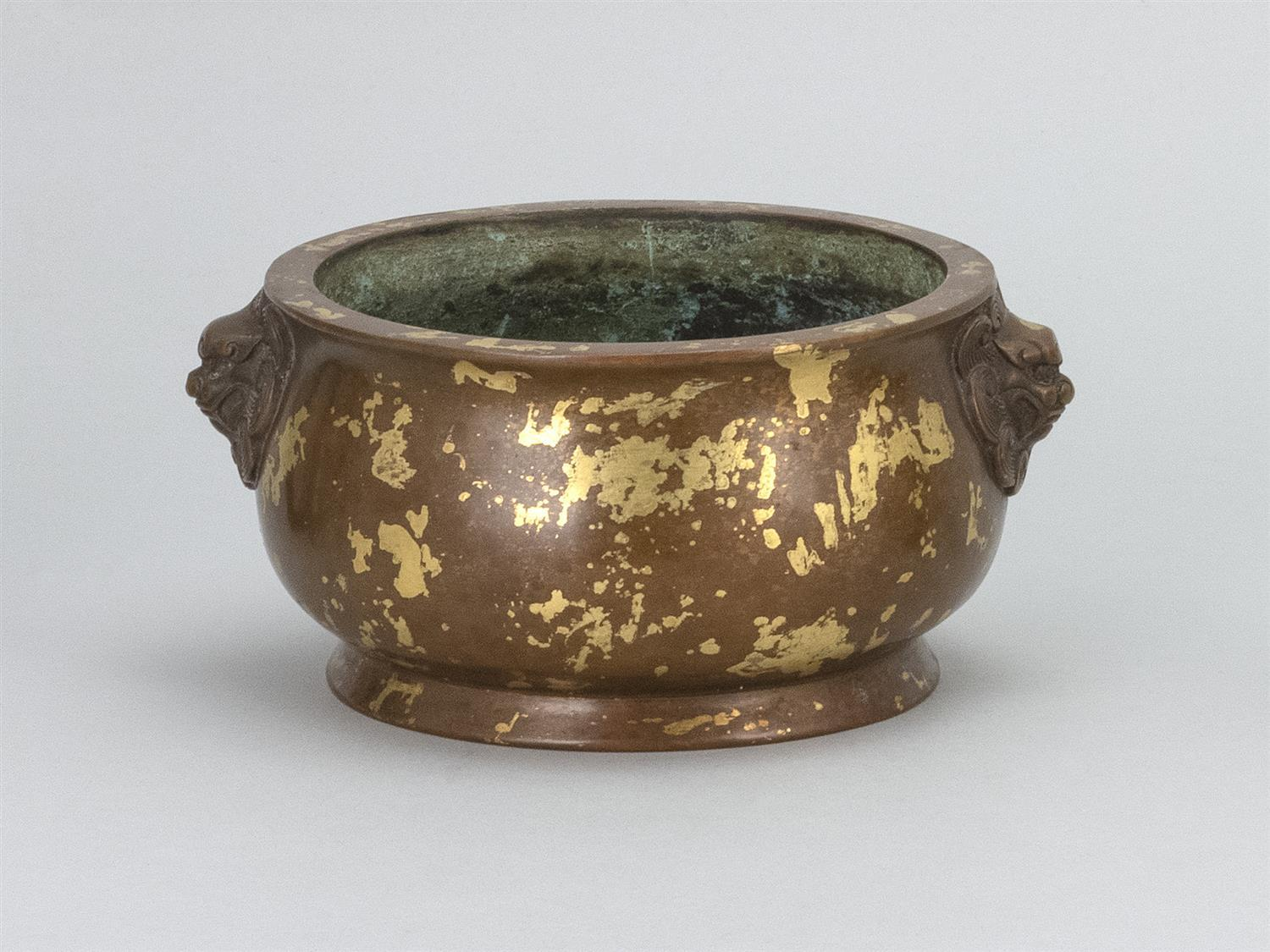 CHINESE SUNSPOT BRONZE CENSER In squat ovoid form, applied mask handles and gilt splashes on a bronze ground. Four-character Xuande...