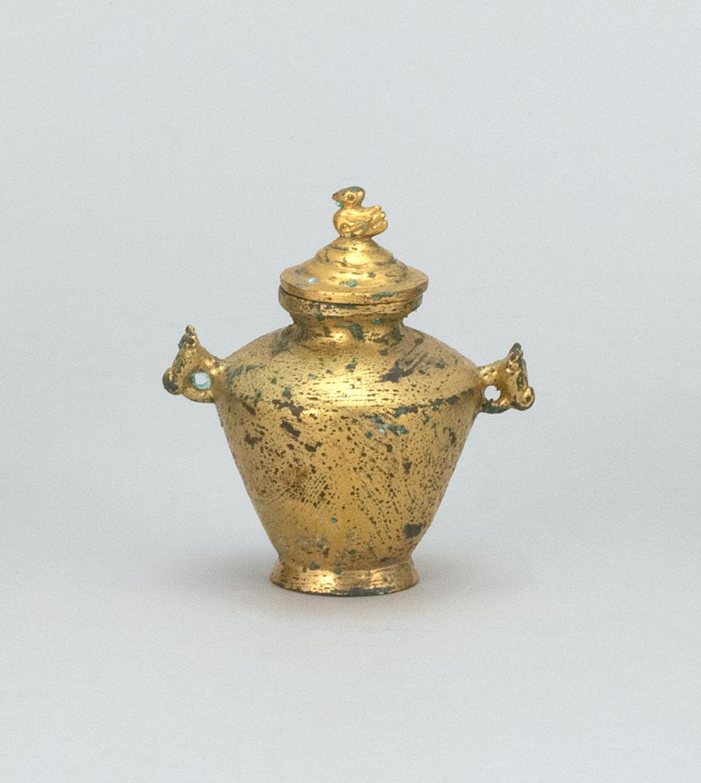 "MINIATURE CHINESE GILT-BRONZE COVERED VASE With animal-head handles and a bird finial. Height 3.25""."