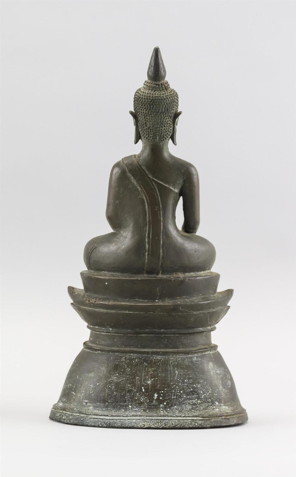 TIBETAN BRONZE FIGURE OF BUDDHA Seated in an earth touching position on a raised oval base. Height 11.5