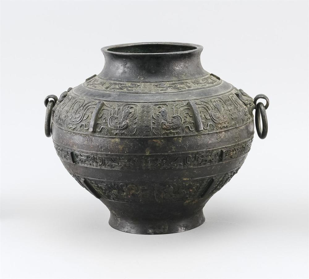 CHINESE ARCHAIC-STYLE BRONZE VASE In inverted pear shape, with mask and loose ring handles and stylized phoenix decoration. Height 8...