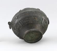 Lot 940: CHINESE ARCHAIC-STYLE BRONZE VASE In inverted pear shape, with mask and loose ring handles and stylized phoenix decoration. Height 8...