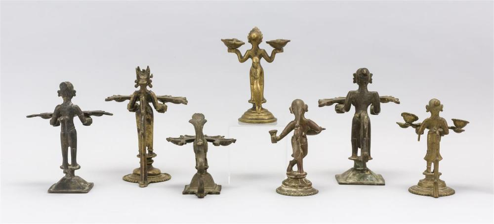 SEVEN INDIAN BRASS OIL LAMPS Five with five wick holders, one in the form of a bird, and one with two wick holders and one with one...