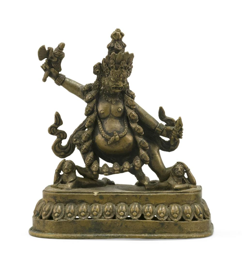 Lot 950: SINO-TIBETAN BRONZE FIGURE OF DHARAMPALA Dancing on two prostrate figures and wearing a necklace of skulls. Openwork lotus base. Hei...
