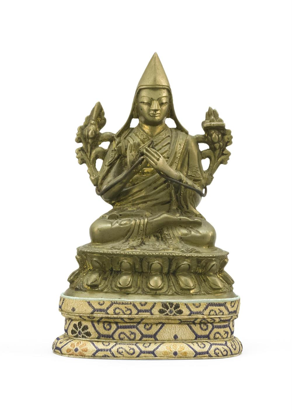 "SINO-TIBETAN BRONZE FIGURE OF A LAMA Seated on a lotus stand. Height 4.25"". Includes a brocade stand."