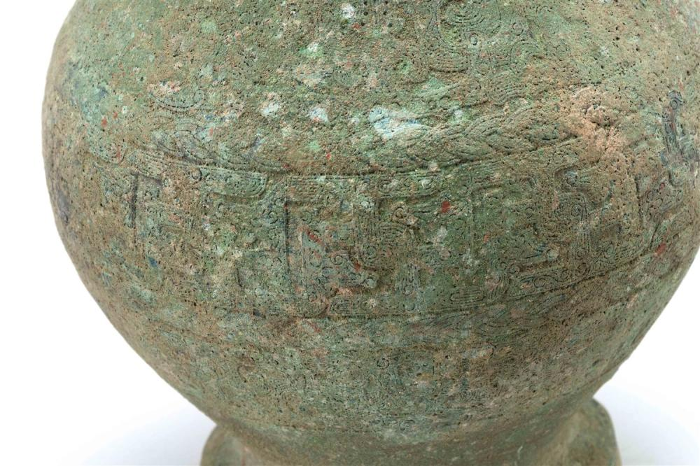 CHINESE BRONZE COVERED HU In baluster form, with animalistic handles. Domed cover with bird finial. Body with fret design. Neck mark...