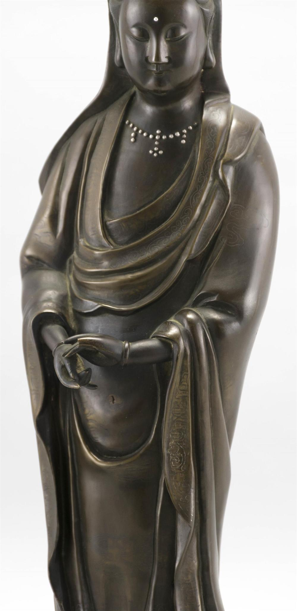 FINELY CAST SHISOU SILVER-INLAID BRONZE FIGURE OF GUANYIN Standing and draped in cloud-inlaid robes. Four-character inscription on b...