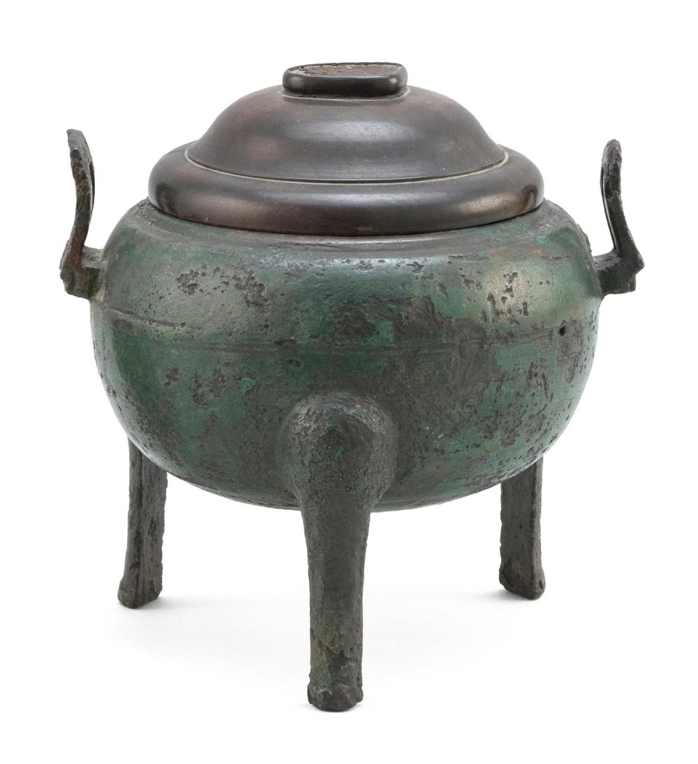 "CHINESE BRONZE DING In ovoid form, with tripod base and rectangular upswept handles. Wood cover. Length 8"". Ex Collection: Henry O...."