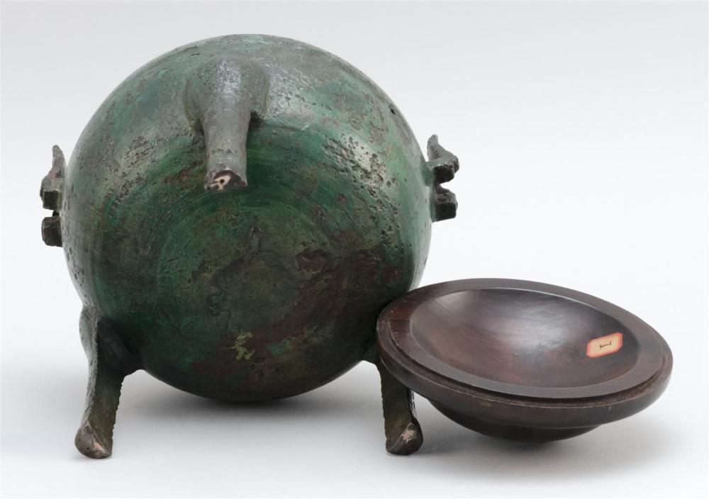 "Lot 960: CHINESE BRONZE DING In ovoid form, with tripod base and rectangular upswept handles. Wood cover. Length 8"". Ex Collection: Henry O...."