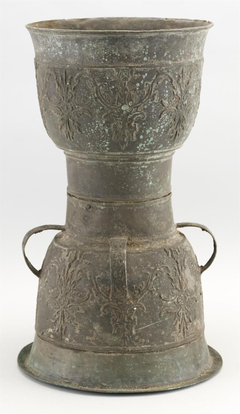 CHINESE BRONZE ARCHAIC-STYLE WAISTED VASE Top and base with raised foliate decoration. Base with loop handles extending to waist. He...
