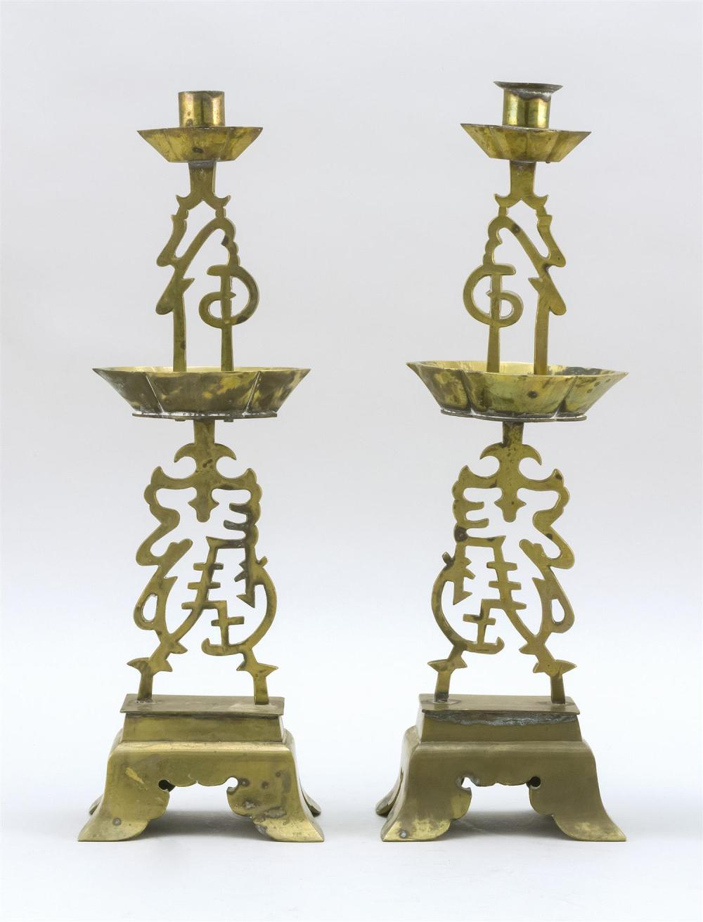 "PAIR OF CHINESE BRASS CANDLESTICKS Openwork calligraphy stems with lozenge-form drip cups. Footed bases. Heights 16""."