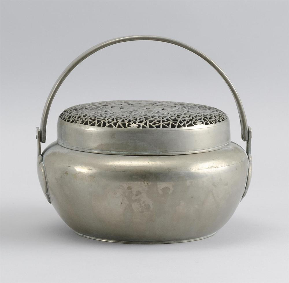 "CHINESE BAITONG FOOT WARMER In ovoid form, with swing handle. Pierced cover in a prunus and cracked ice design. Diameter 7.5""."