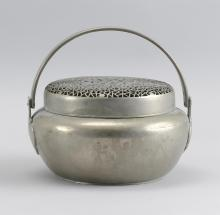 """Lot 965: CHINESE BAITONG FOOT WARMER In ovoid form, with swing handle. Pierced cover in a prunus and cracked ice design. Diameter 7.5""""."""