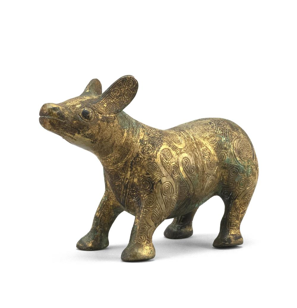 "CHINESE GILT-BRONZE FIGURE OF A TAPIR With engraved scrolling decoration about the body. Height 4.5"". Length 8""."