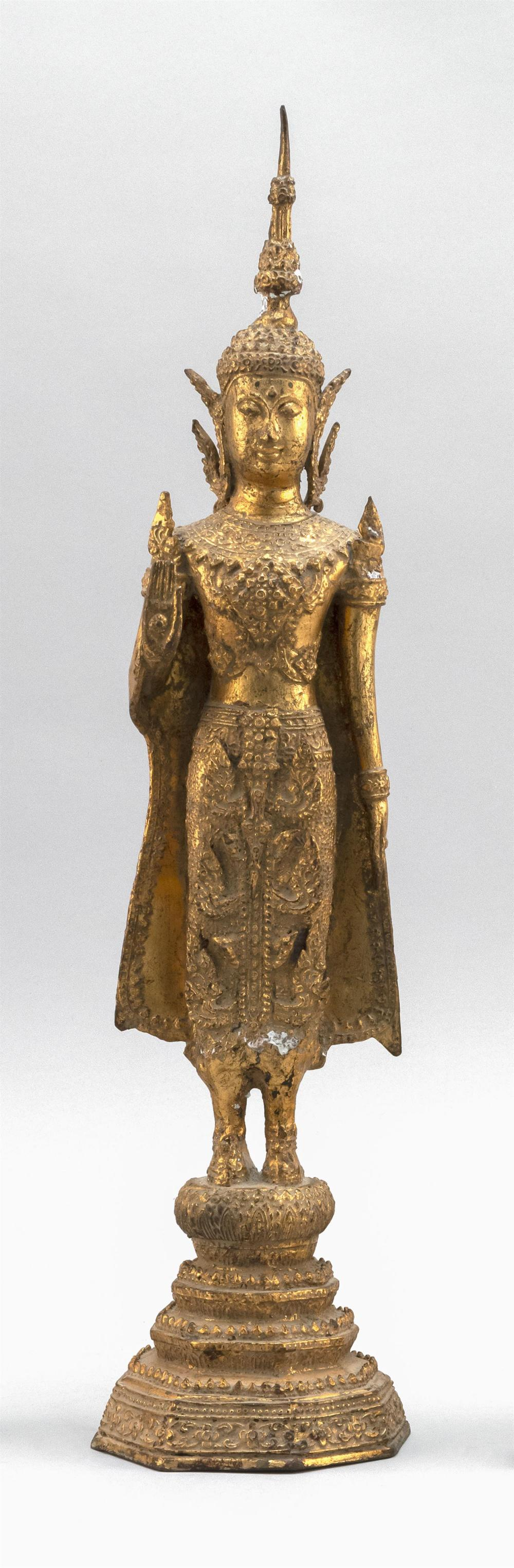 TIBETAN GILT-BRONZE FIGURE OF BUDDHA Standing on a conforming tiered base, dressed in ceremonial headdress and robes and with the ri...