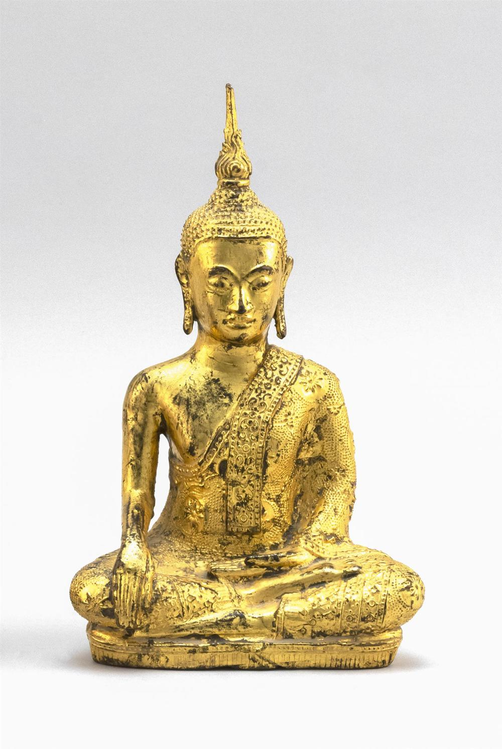 "TIBETAN GILT-BRONZE FIGURE OF BUDDHA Seated in earth touching position. Height 10"". Length 6""."