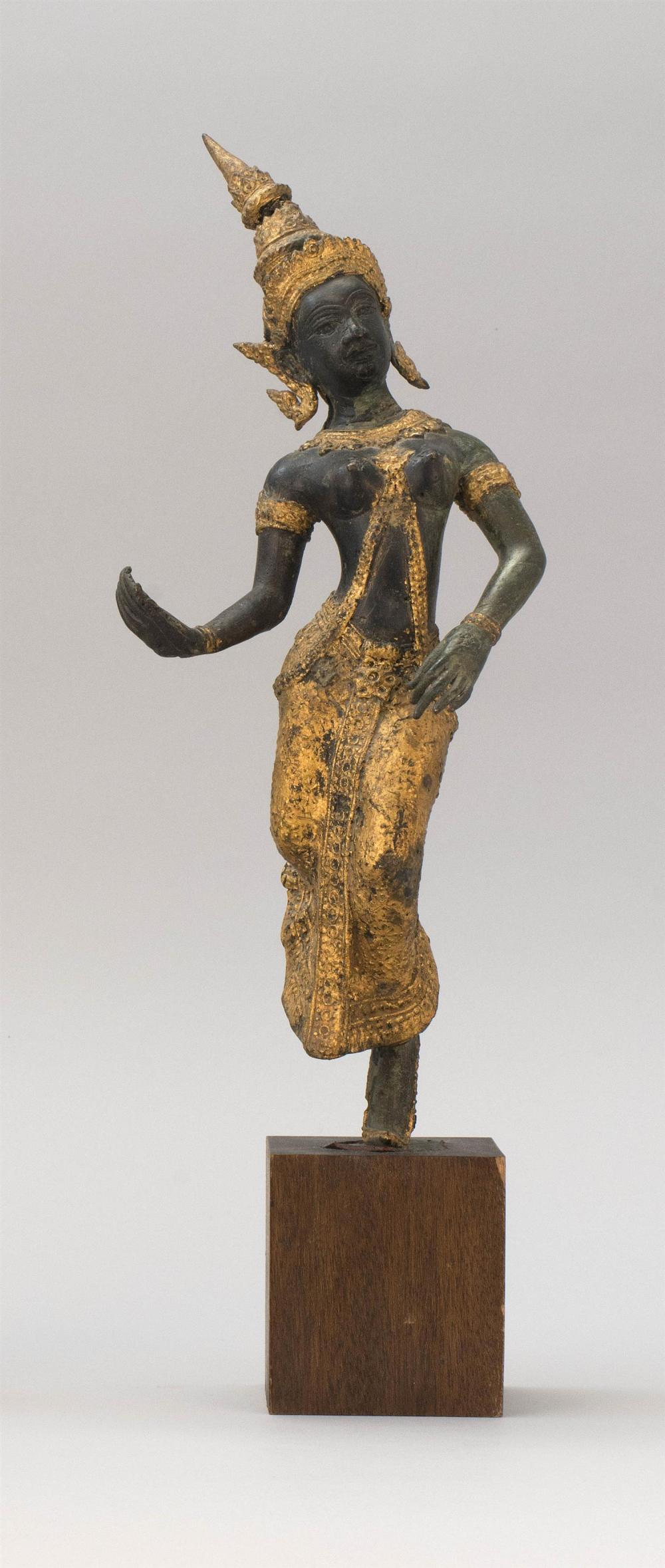 "THAI GILT-BRONZE FIGURE OF A DANCER Wearing a pointed headdress and flowing skirt. Height 13.5"". Wood stand."
