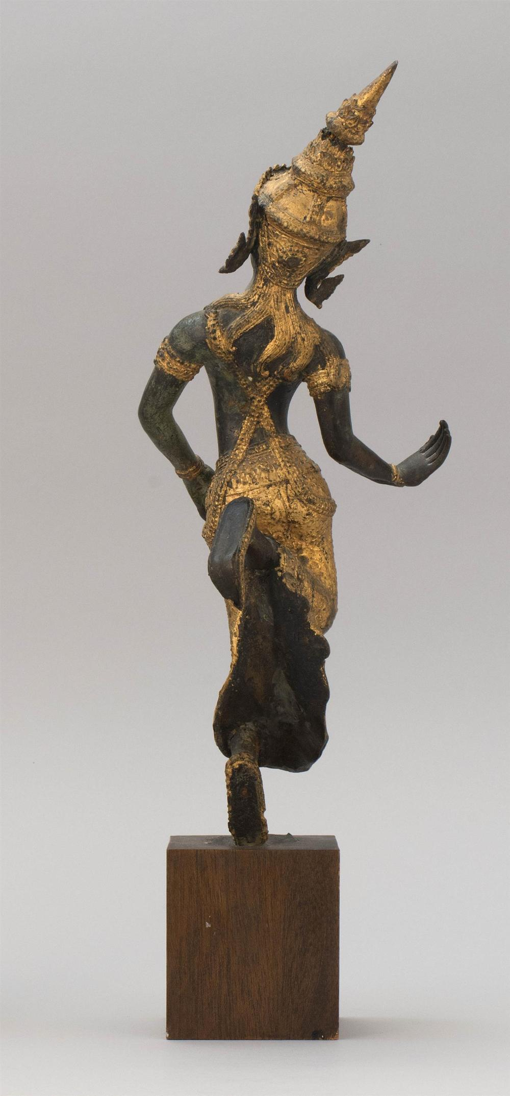 """Lot 974: THAI GILT-BRONZE FIGURE OF A DANCER Wearing a pointed headdress and flowing skirt. Height 13.5"""". Wood stand."""