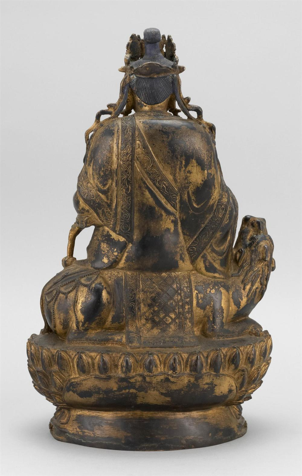 Lot 978: CHINESE PARTIAL-GILT FIGURE OF BUDDHA Seated on a guardian lion atop a two-tier lotus base. Traces of gilding and polychroming. Heig...