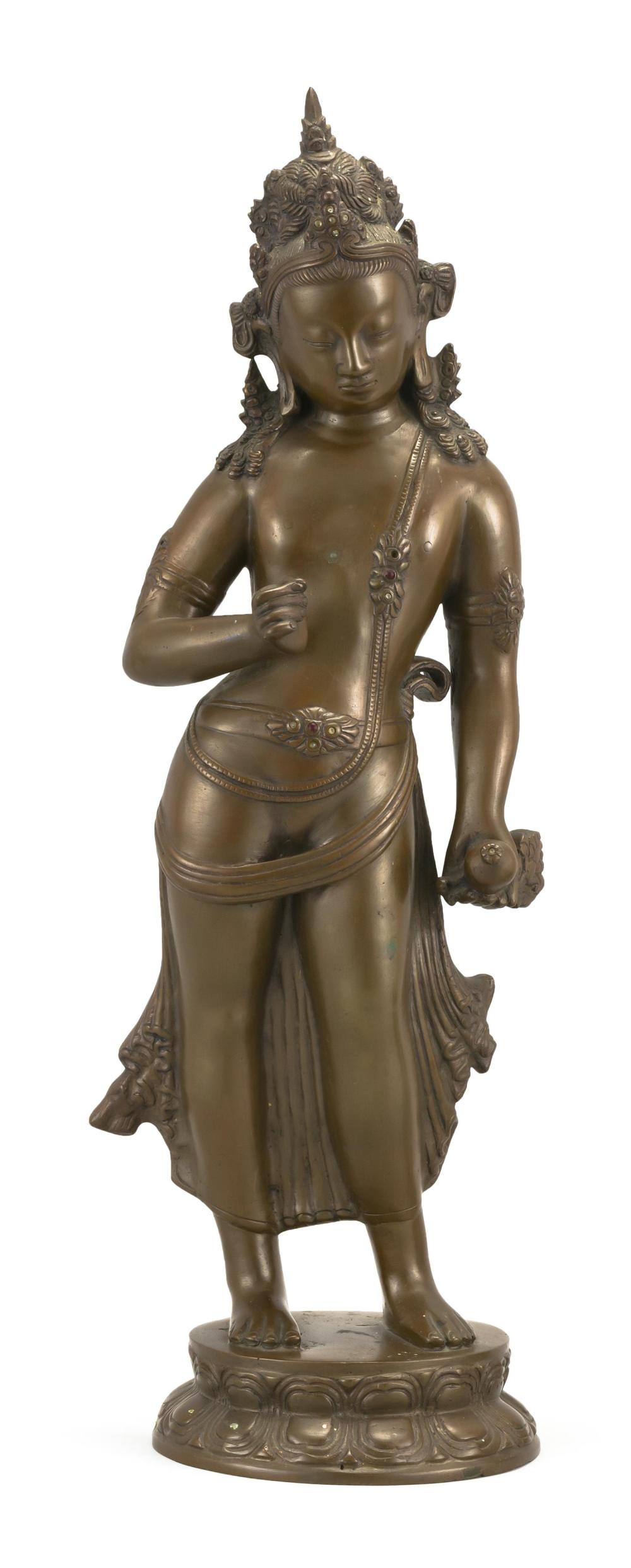 "INDIAN BRONZE FIGURE OF TARA Standing on a lotus base. Height 19.5""."