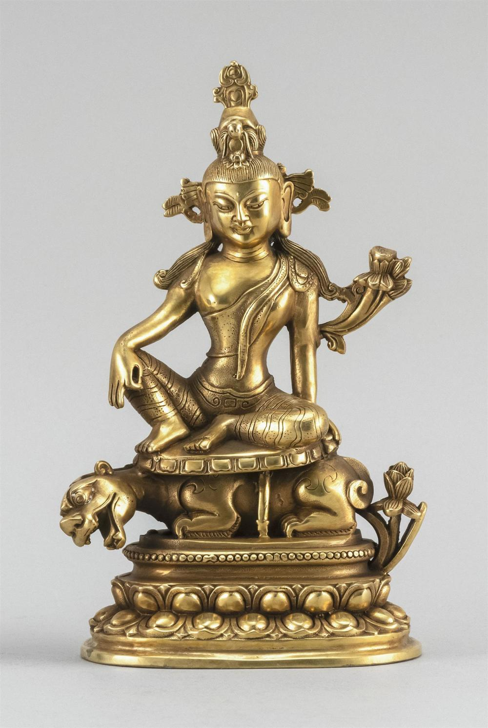"CHINESE GILT-BRONZE FIGURE OF A DEITY Seated on a tiger atop a double lotus base. Height 8.5""."