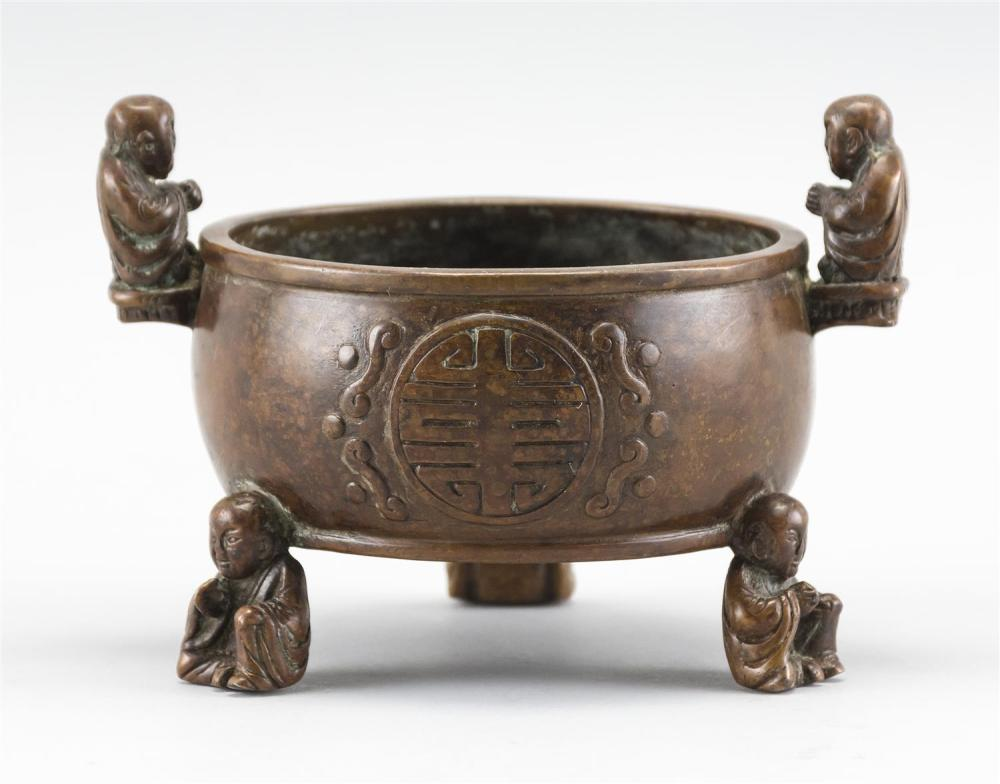 CHINESE BRONZE INCENSE BURNER In drum form, with three figural feet and two figural handles. Body with shou design. Six-character Mi...