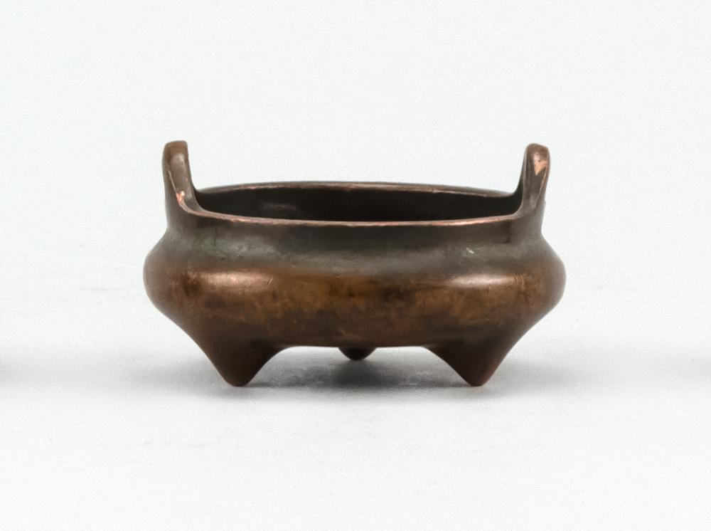 "MINIATURE CHINESE BRONZE CENSER In squat ovoid form, with tripod base and loop handles. Two-character mark on base. Diameter 2.3""."