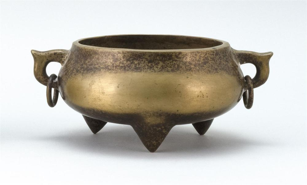 CHINESE BRONZE CENSER With two loose ring handles and trifoot base. Uneven patina. Four-character mark on base.