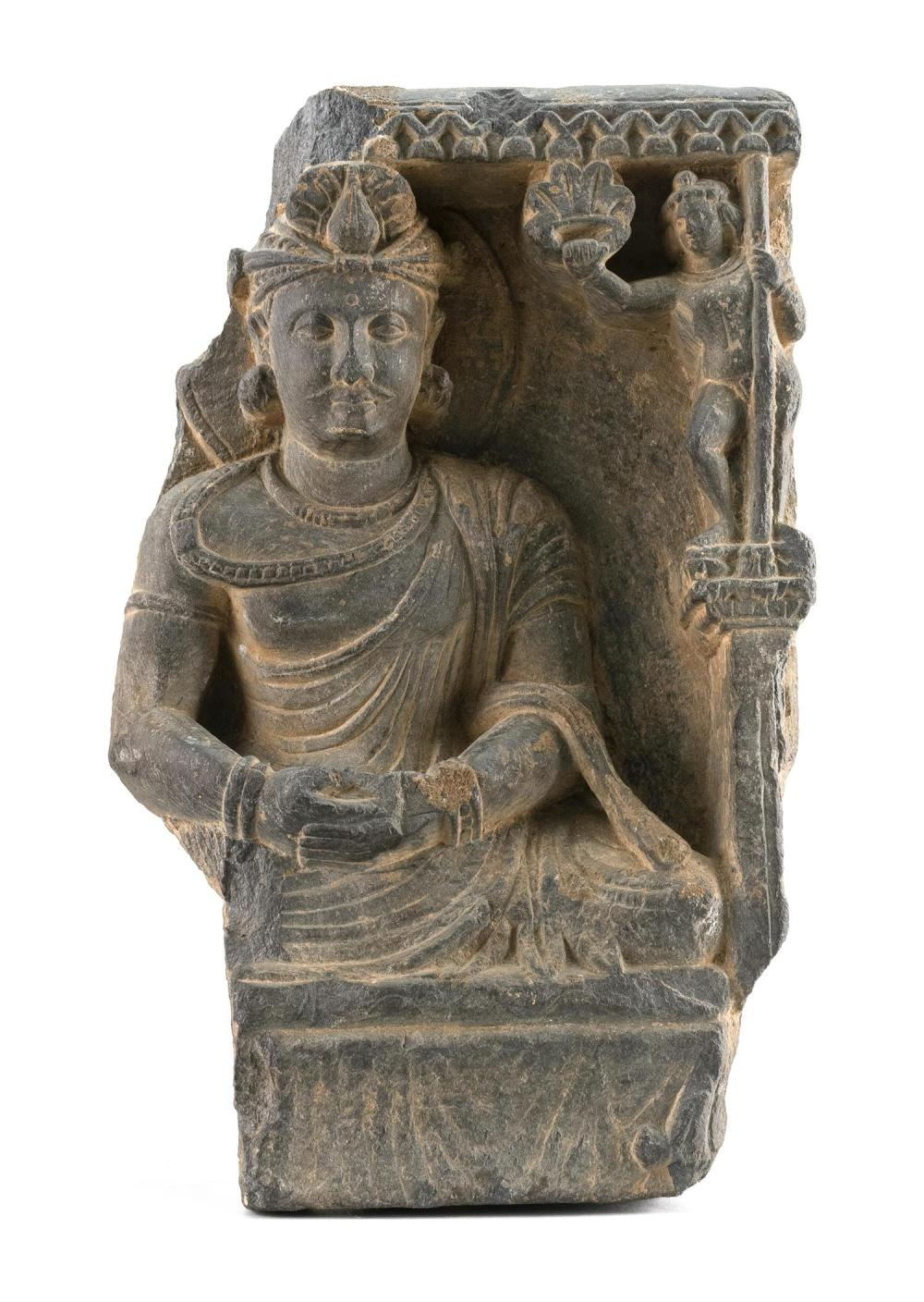 "GANDHARAN RELIEF BLACK STONE PANEL Depicting a seated deity with one attendant. Fragment of a larger sculpture. Height 11""."