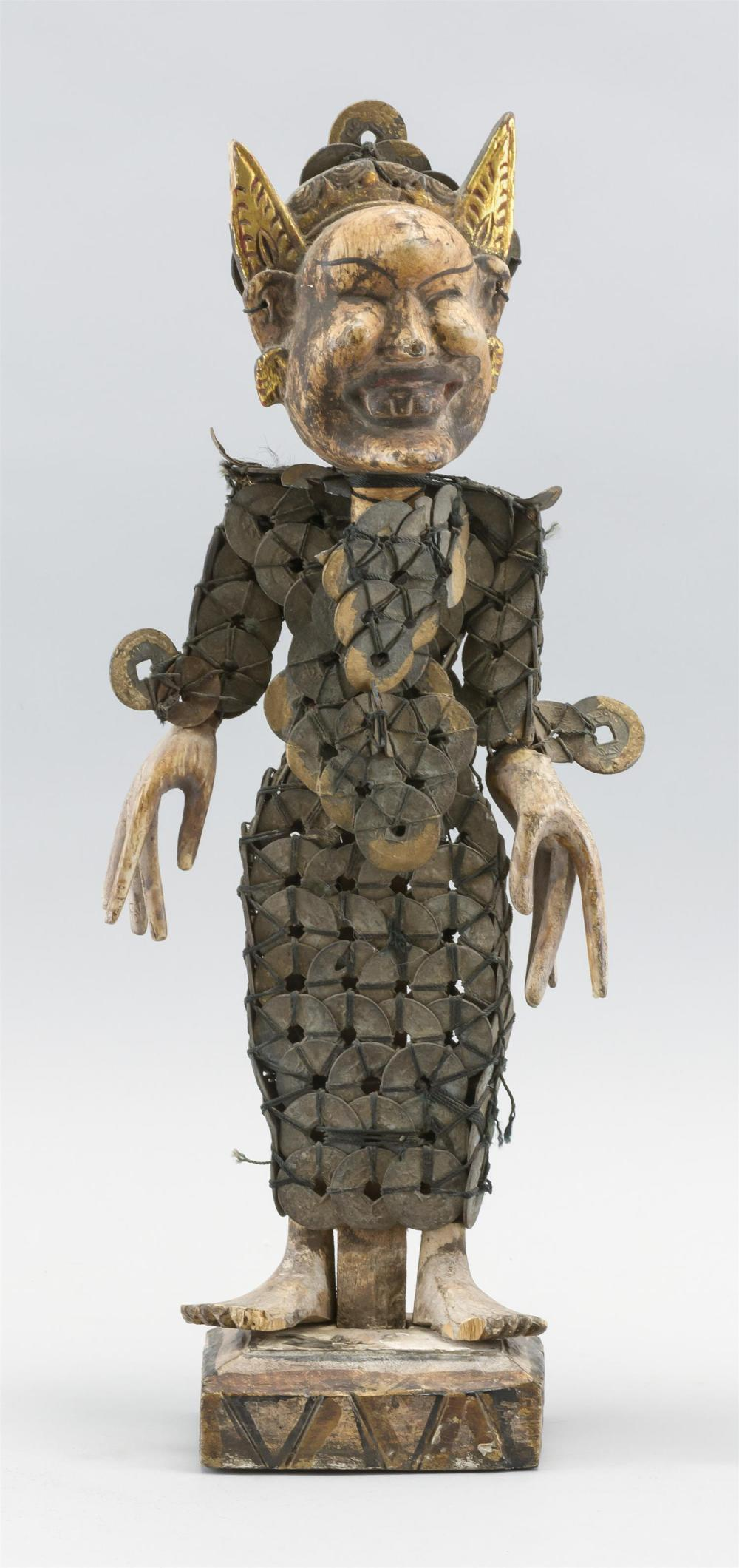 "SOUTHEAST ASIAN WOOD AND COIN FIGURE OF A HORNED DEMON Standing on a platform. Height 5""."