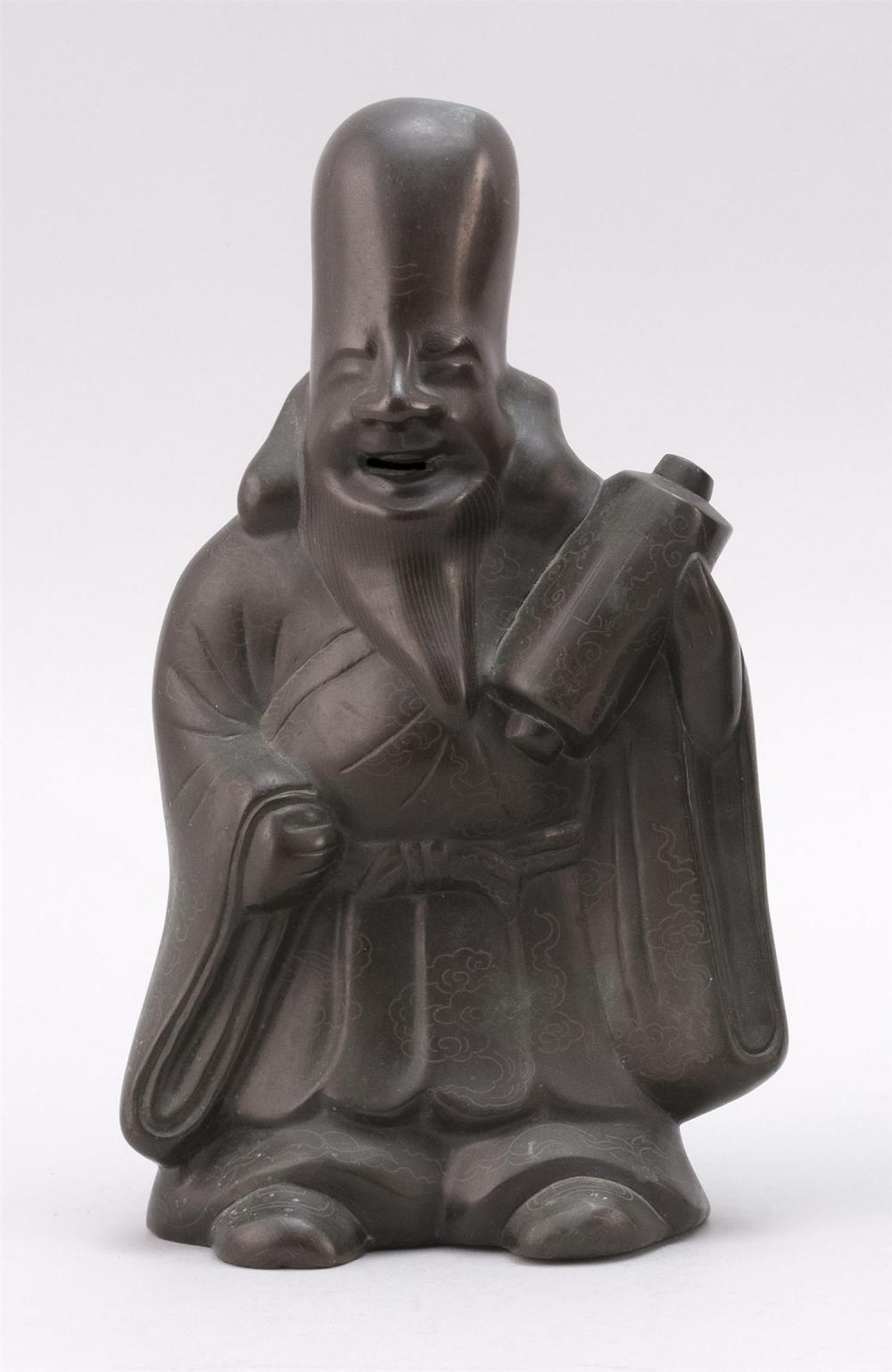 "BRONZE FIGURE OF A SMILING SCHOLAR Standing and holding a scroll. Allover incised cloud pattern. Height 9"". Width 6""."