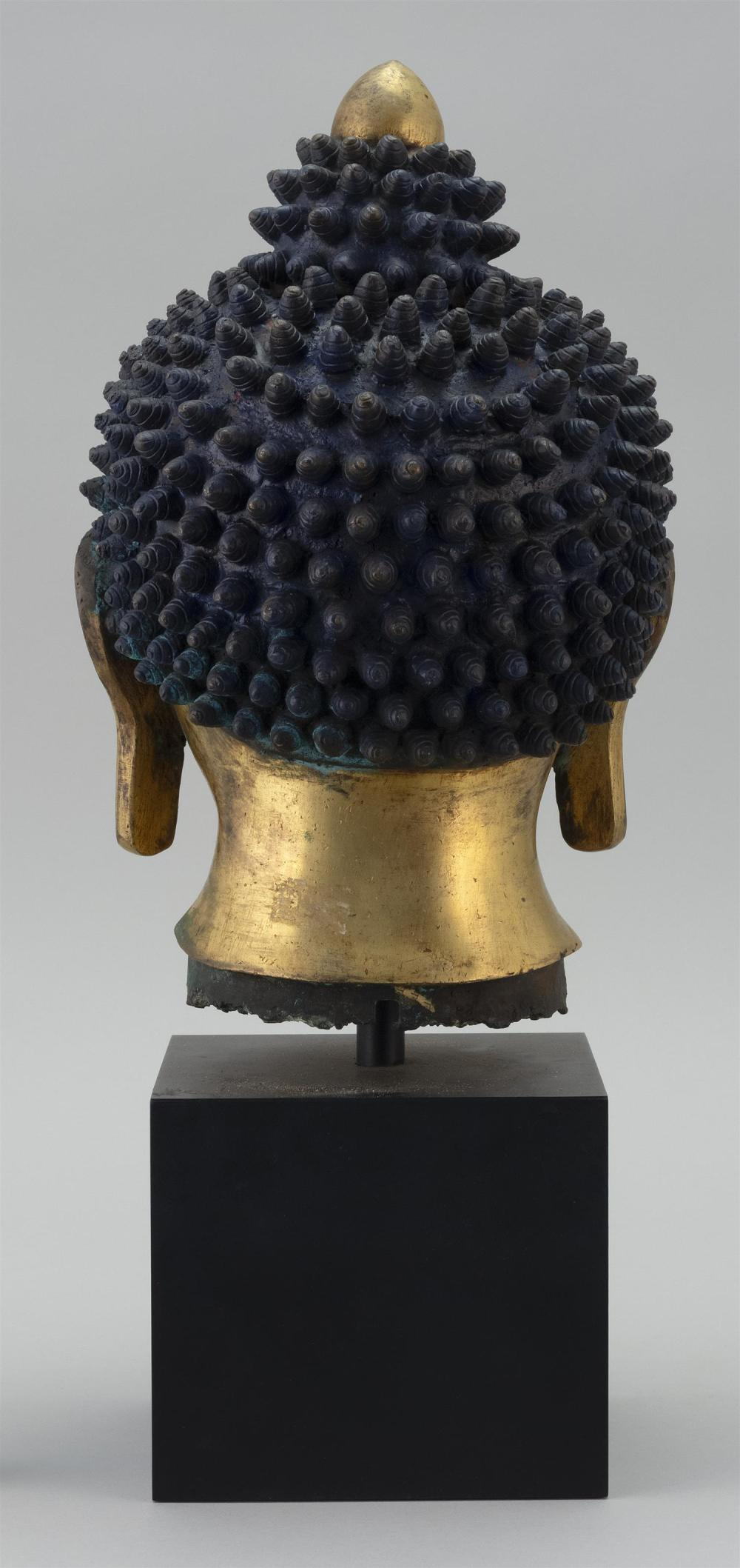"""Lot 1002: GILT-BRONZE HEAD OF BUDDHA With tightly curled top knots. Shaded in blue. Height 9.25""""."""