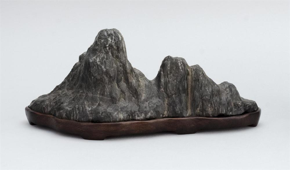"""Lot 1008: CHINESE BLACK STONE SCHOLAR'S ROCK In mountain range form. Wood base. Length 13.25""""."""
